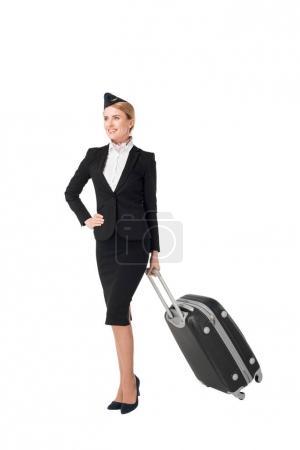 Stewardess in uniform holding suitcase isolated on white