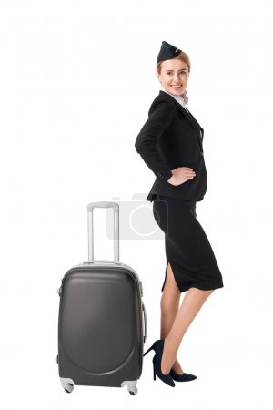 Young stewardess in uniform by suitcase isolated on white
