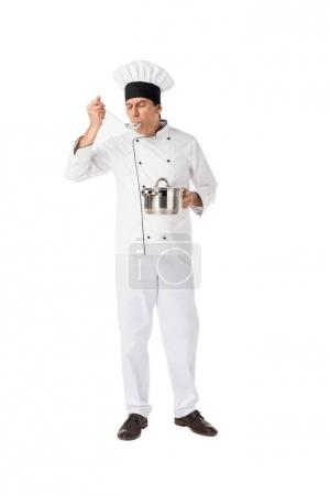 Smiling chef with pan tasting food isolated on white