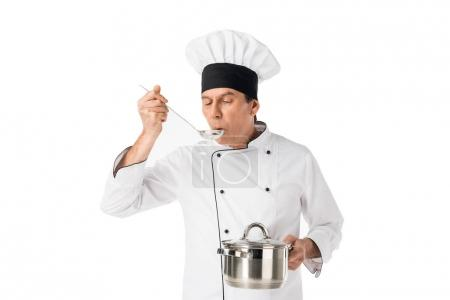 Man in chef uniform holding pan and tasting food isolated on white