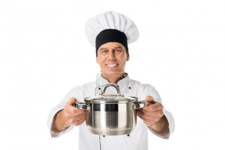 Chef in uniform and toque blanche holding pan isolated on white