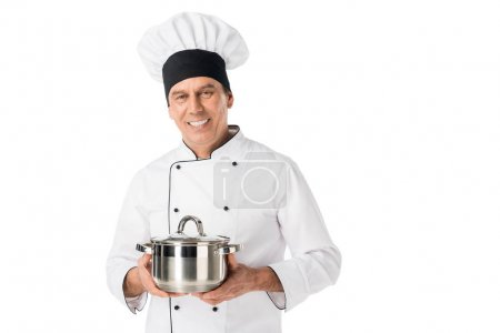Smiling man in chef uniform holding pan isolated on white