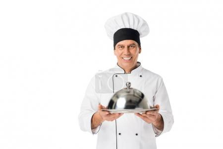 Chef in uniform and toque blanche holding tray with cover isolated on white