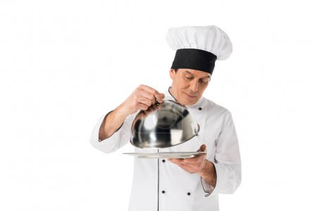 Man in chef uniform looking on tray with cover isolated on white