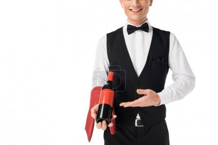Smiling professional waiter presenting wine bottle isolated on white