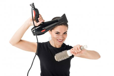 Smiling female hairdresser with dryer and hairbrush isolated on white