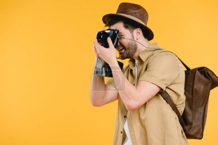 side view of young man in hat with backpack photographing with camera isolated on yellow