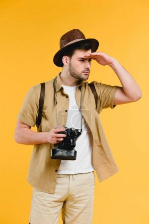 young male traveler in hat holding camera and looking away isolated on yellow