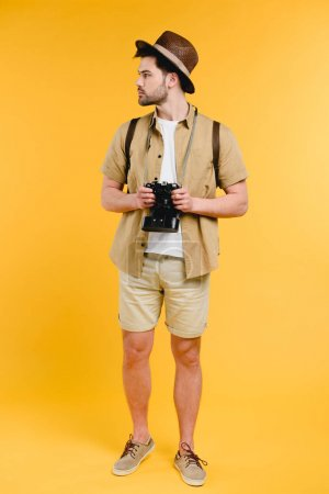 young male traveler in shorts holding camera and looking away isolated on yellow