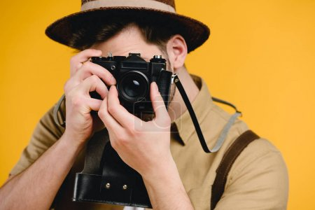 young male photographer photographing with camera isolated on yellow