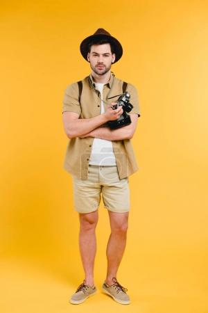 Handsome young traveler in shorts and hat holding camera isolated on yellow