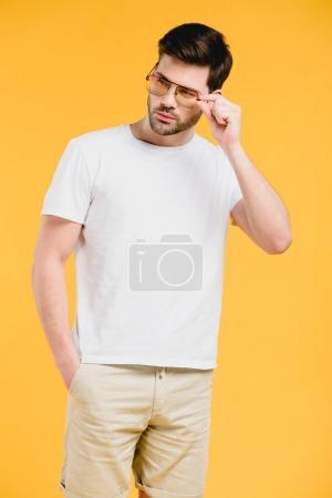Photo pour Beau jeune homme barbu en t-shirt blanc ajustant les lunettes de soleil et regardant loin isolé sur jaune - image libre de droit