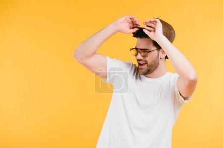 Photo pour Beau jeune homme souriant avec des lunettes de soleil ajustant chapeau et regardant loin isolé sur jaune - image libre de droit