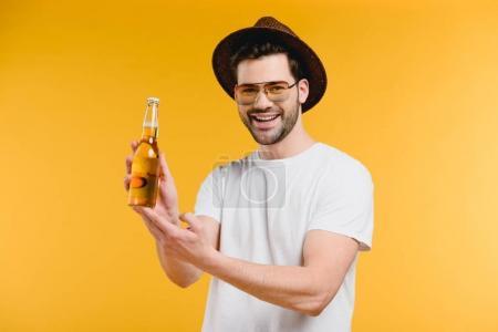 young man in hat and sunglasses showing glass bottle with summer drink and smiling at camera isolated on yellow