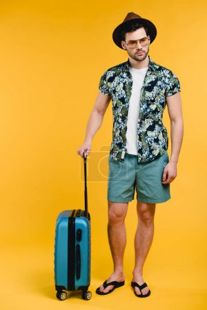 Photo for Full length view of handsome young man in summer outfit holding suitcase isolated on yellow - Royalty Free Image