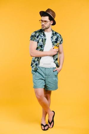 handsome young man in summer outfit holding glass bottle of refreshing beverage and looking away isolated on yellow