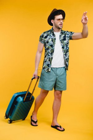 young man with suitcase looking away and waving hand isolated on yellow