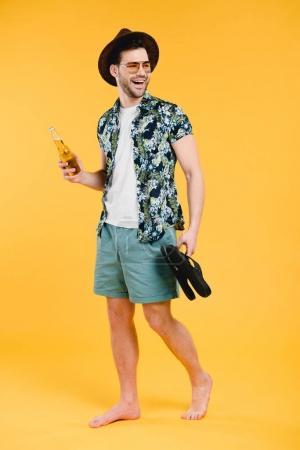 Foto de Sonriente joven descalza en cortos sosteniendo la botella de bebida de verano y sandalias aislados sobre fondo amarillo - Imagen libre de derechos
