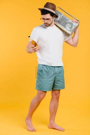 young barefoot man in shorts holding tape recorder on shoulder and looking at glass bottle of summer drink isolated on yellow