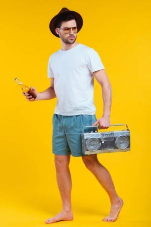young barefoot man in shorts holding tape recorder and bottle of summer drink isolated on yellow