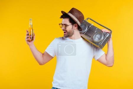 Photo pour Gai jeune homme au chapeau et des lunettes de soleil tenant le magnétophone et bouteille de boisson d'été isolé sur jaune - image libre de droit