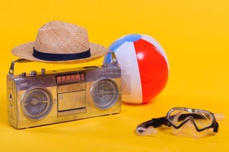 Photo pour Magnétophone, bonnet, ballon de plage et snorkeling avec masque de plongée isolé sur jaune - image libre de droit