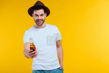 handsome young man in hat holding glass bottle of summer drink and smiling at camera isolated on yellow