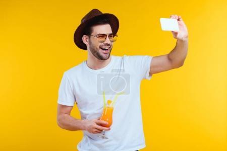 Photo pour Gai jeune homme tenant le verre de selfie cocktail et en s'occupant de l'été avec le smartphone isolé jaune - image libre de droit