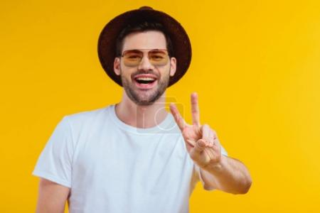 cheerful young man in white t-shirt, hat and sunglasses showing victory sign and smiling at camera isolated on yellow