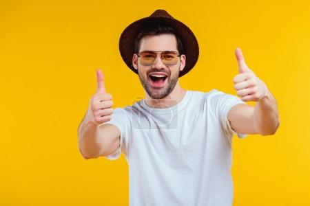 Cheerful young man in white t-shirt, hat and sunglasses showing thumbs up and smiling at camera isolated on yellow