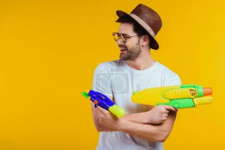 Photo for Smiling young man in hat and sunglasses playing with water guns isolated on yellow - Royalty Free Image