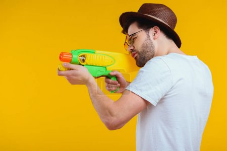 side view of bearded young man in hat and sunglasses shooting with water gun isolated on yellow