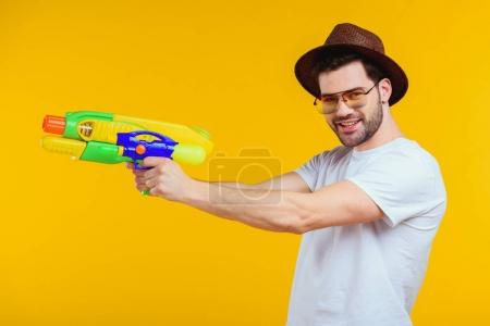 stylish young man holding water gun and smiling at camera isolated on yellow