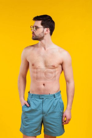 handsome shirtless young man in shorts and sunglasses standing with hand in pocket and looking away isolated on yellow