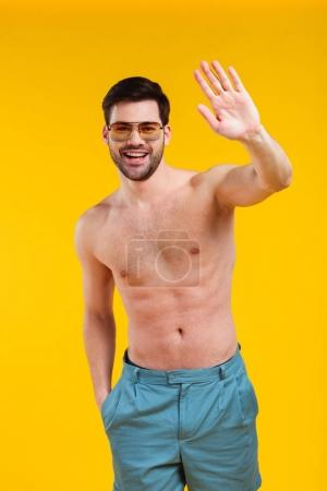 handsome shirtless young man in shorts and sunglasses waving hand and smiling at camera isolated on yellow