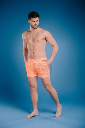 full length view of handsome barefoot man in shorts standing with hands in pockets and looking away on blue