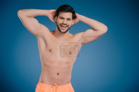 handsome shirtless young man standing with hands behind head and smiling at camera on blue