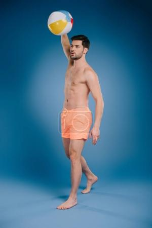 full length view of young barefoot man in shorts throwing beach ball and looking away on blue