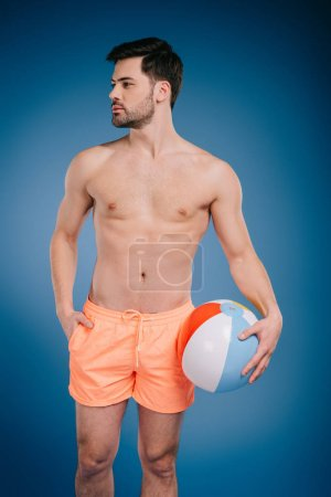 handsome young shirtless man in shorts holding beach ball and looking away on blue