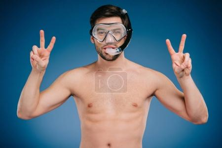 young man in snorkel and diving mask showing victory sign and looking at camera on blue