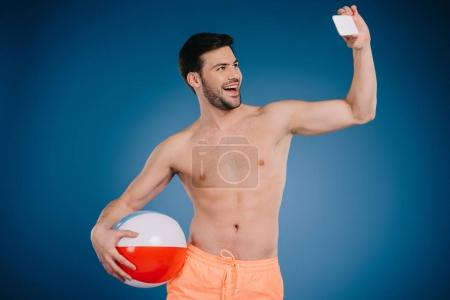 smiling young man in shorts holding beach ball and taking selfie with smartphone on blue