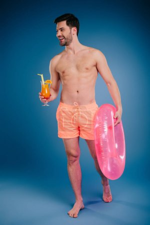 smiling young man in shorts holding glass of summer cocktail and inflatable ring on blue