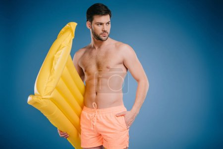 handsome young man in shorts holding swimming mattress and looking away on blue