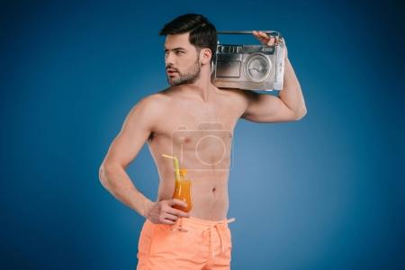 handsome young man in shorts holding tape recorder and glass of summer cocktail on blue
