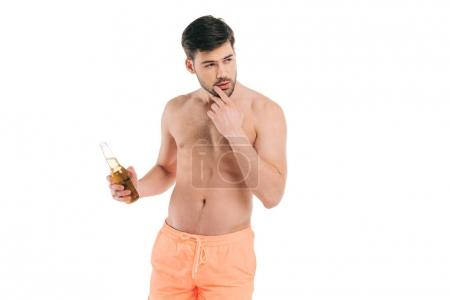 handsome young shirtless man in shorts holding bottle of summer drink and looking away isolated on white