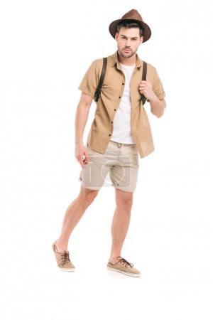 full length view of handsome young traveler with backpack looking at camera isolated on white
