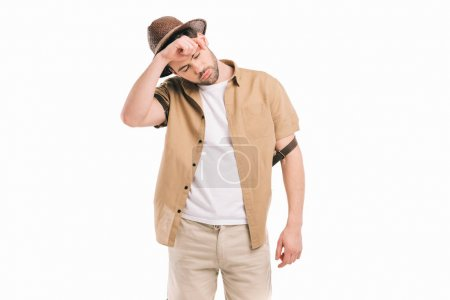 tired young traveler in hat wiping sweat isolated on white