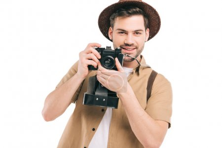Handsome smiling young man in hat holding camera isolated on white