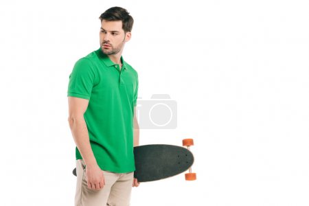 handsome young man holding skateboard and looking away isolated on white