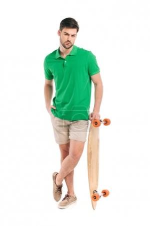 stylish young man leaning at skateboard and looking at camera isolated on white